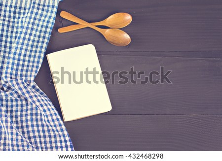 book with recipes, cloth and 2 wooden spoons on a dark background - stock photo