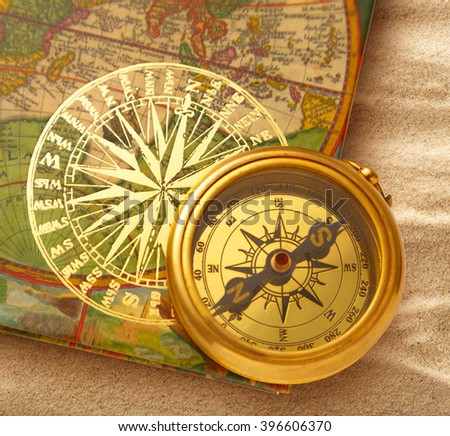 Book with retro golden compass on sand - stock photo