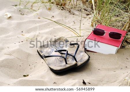 book with sunglases and shoes on the beach - stock photo