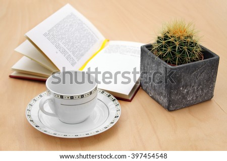 Book with the cactus and a cup                   - stock photo