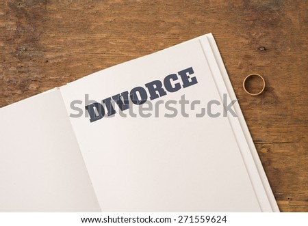 Book with title Divorce and blank white page. One wedding ring on the side. Empty space for copy. Conceptual image of divorce. - stock photo
