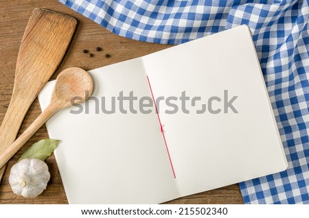 Book with wooden spoons on a blue checkered tablecloth - stock photo