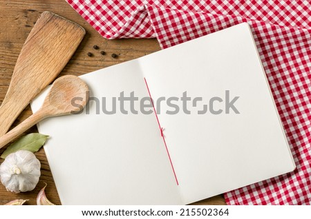 Book with wooden spoons on a red checkered tablecloth - stock photo