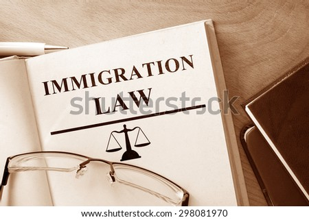 Book with words Immigration Law and glasses. - stock photo