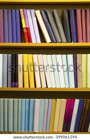 bookcase with many books in different colors - stock photo
