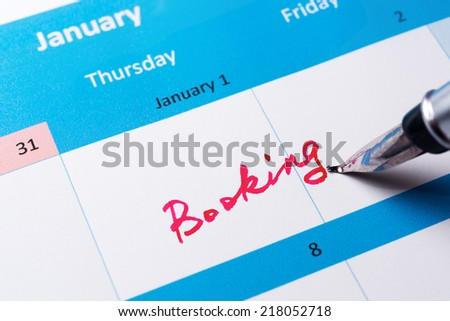 Booking word written on the calendar with a pen - stock photo