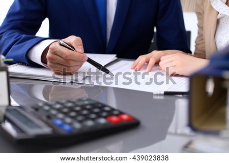 Bookkeeper or financial inspector and secretary making report, calculating or checking balance. Internal Revenue Service inspector checking financial document. Audit concept.  - stock photo