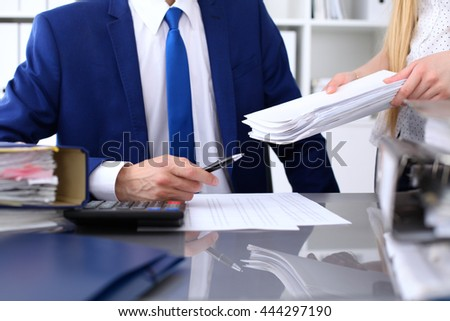 Bookkeeper or financial inspector and secretary making report, calculating or checking balance.  Audit concept.