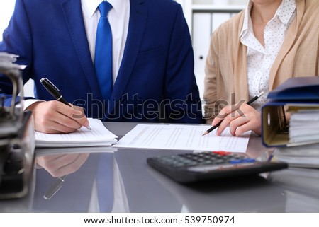 Bookkeeper or financial inspector and secretary making report, calculating or checking balance. Internal Revenue Service inspector checking financial document. Audit concept.