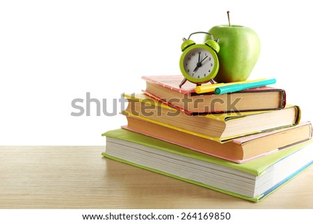 Books, alarm clock and apple on desk, isolated on white - stock photo