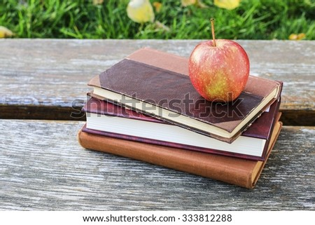 Books and apple in the garden - stock photo