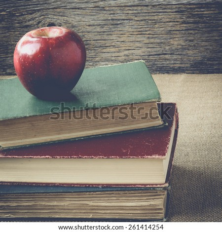 books and apple  on retro background with Instagram Style Filter - stock photo