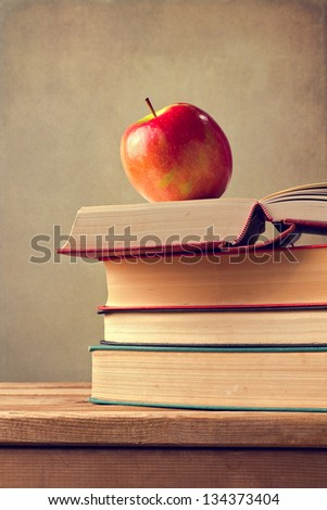 Books and apple on wooden table over grunge background.