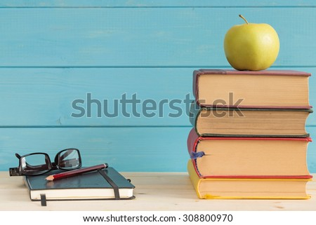 Books and apple with a notebook pencil and glasses on a rustic background. - stock photo