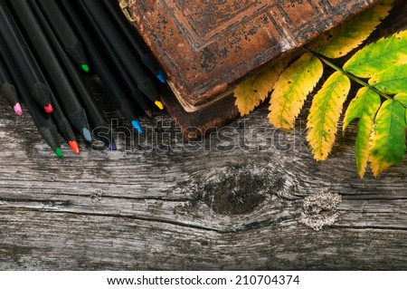 Books and autumn leaves on wooden table close-up - stock photo