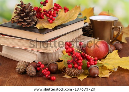 Books and autumn leaves on wooden table on natural background - stock photo