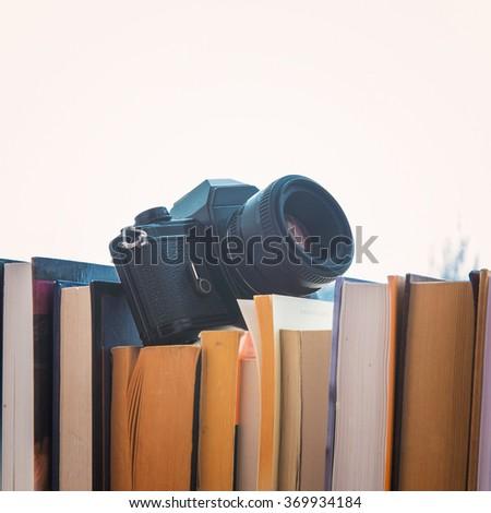 books and camera stand on a windowsill near the window - stock photo