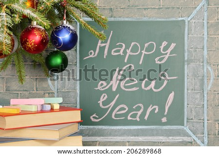 Books and Christmas decorations before chalkboard with title: Happy New Year! - stock photo