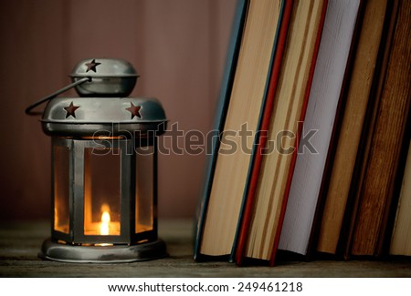 Books and decorative lantern on table and wooden planks background