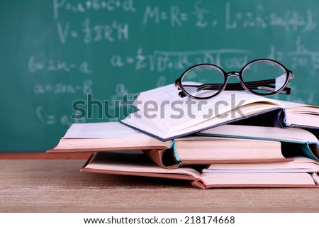 Books and glasses on wooden table on blackboard background - stock photo