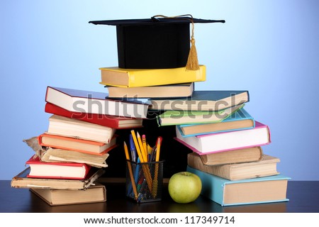 Books and magister cap against school board on wooden table on blue background - stock photo