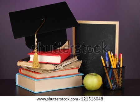 Books and magister cap against school board on wooden table on purple background - stock photo