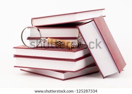 books and magnifying glass isolated on white - stock photo