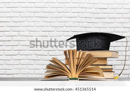 books and mortarboard on wooden table - stock photo