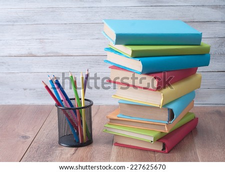 Books and pencils on a wooden background.