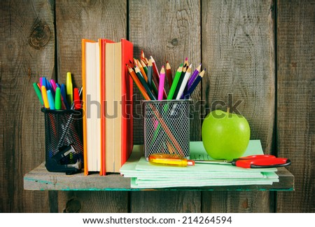 Books and school tools on a wooden shelf. A wooden background.