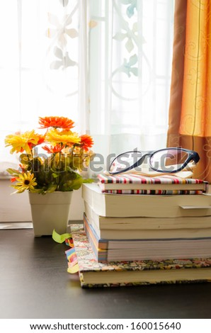 books and the glasses on table, near windows. - stock photo