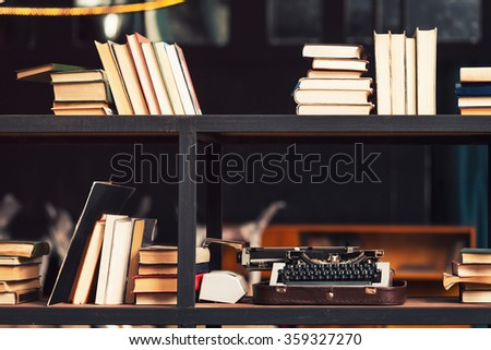 Books and typewriter on wooden shelfs in the interior