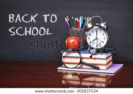 Books, apple, alarm clock and pencils on wood desk table. Text back to school on black board concept - stock photo