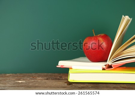 Books, apple and chalk on blackboard background