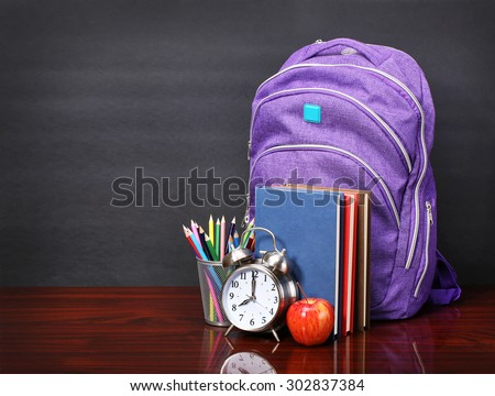 Books, apple, backpack, alarm clock and pencils on wood desk table and black board. Back to school concept - stock photo