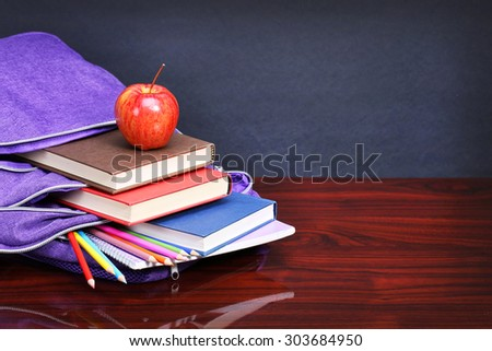 Books, apple, backpack and pencils on wood desk table and black board. Back to school concept - stock photo
