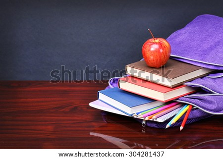 Books, apple, backpack and pencils on wood desk table and black board. back to school concept