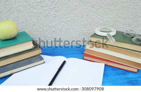 Books, apple, notebook,reading glasses, pencils on wood desk table and black board. Back to school concept.autumn - stock photo