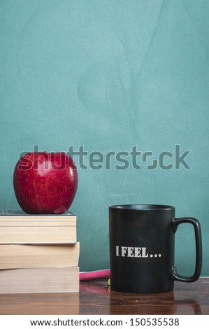 books coffee mug and apple in front of green chalkboard - stock photo