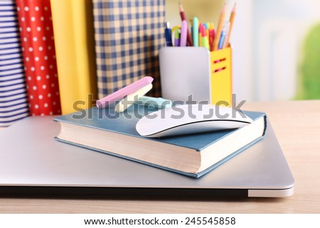 Books, computer mouse and pieces of chalk on wooden table and light background - stock photo
