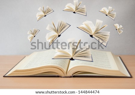 Books flying away from open book on the desk. Education concept