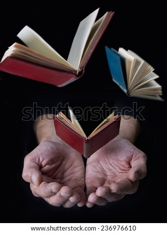 Books flying from hands, on black background - stock photo