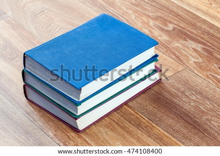 Books in a firm cover lie one on one on a surface of a wooden table.