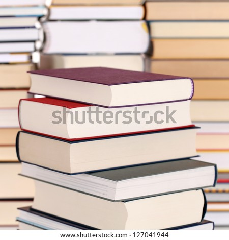 Books in a stack, with more books forming a background - stock photo