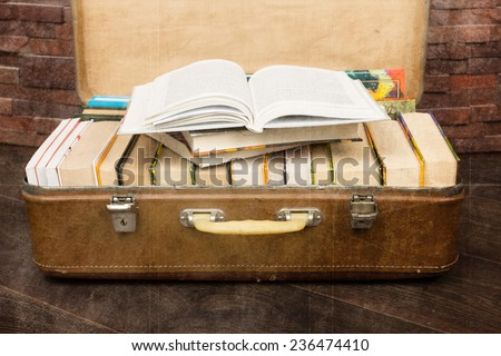 Books in a vintage suitcase. Retro look with added texture - stock photo