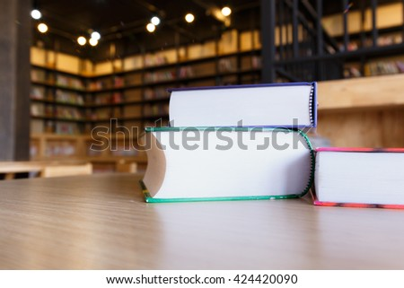 Books in public library and blurred book shelves. - stock photo