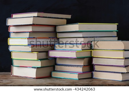 Books in stacks on the table in the background of a school blackboard. Back to school.