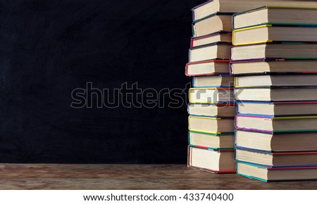 Books in stacks on the table in the background of a school blackboard. Back to school. Left empty space for Your text. - stock photo