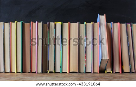 Books in the colored covers on the shelf in the background of a school blackboard.