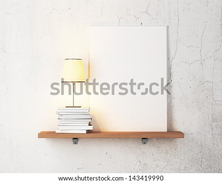 books, lamp and blank poster on a shelf  - stock photo